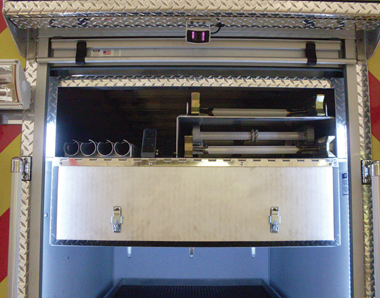 KME built this ladder compartment that runs up through the center ceiling area of a rescue truck that uses typically unusable space behind the body side compartment roll-up doors.