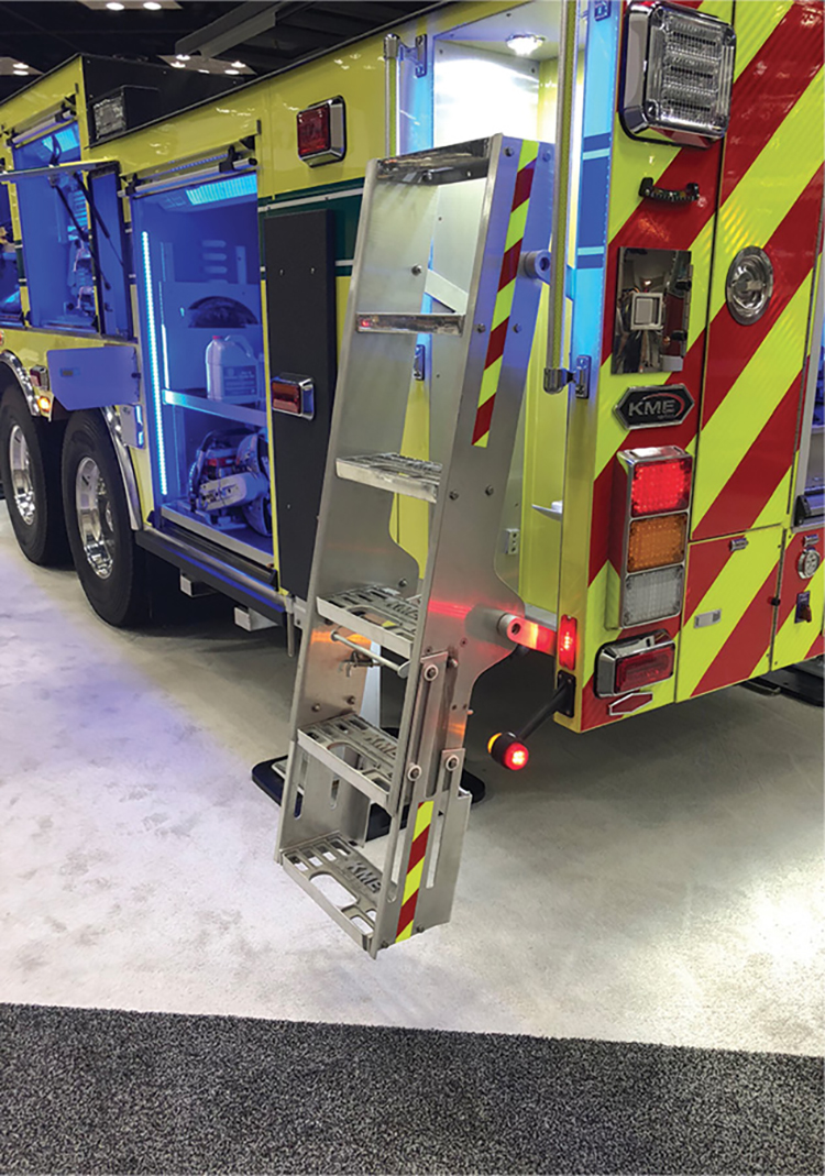 This KME apparatus has a hinged ladder that pivots out of its storage receptacle with a retractable bottom step. There is sufficient light near the ladder, and it has two hand rails for overall firefighter safety.
