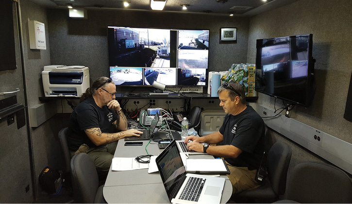 The conference room table with live-feed wall monitors and communications equipment.