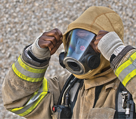 A firefighter dons a PGI Cobra BarriAire™ Gold Hood that inhibits penetration of harmful contaminants and particulates. (Photo courtesy of PGI Inc.)