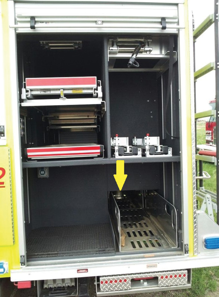 A slide-out tray in a rear side compartment on a rescue-pumper. The Storz hose connection is just visible above the tray. There's another preconnect on the opposite side.