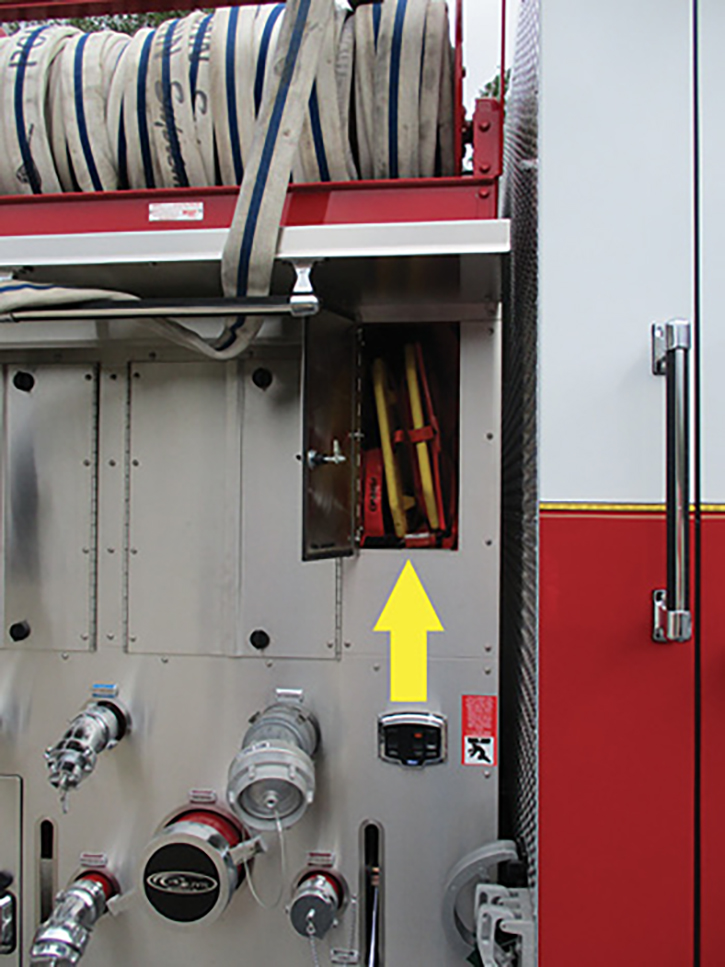 The arrow shows the backboard storage compartment. Below the arrow is an auxiliary controller for the 4-inch LDH discharge. To the left are double-hinged pump panel access doors.