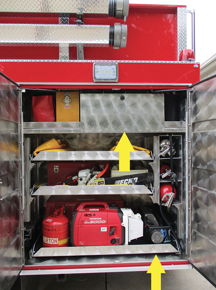 The compartment on the road side behind rear wheels. A drop-down door protects six spare SCBA bottles. A portable electric winch is on the right side of the floor-mounted tray. Heavy equipment is mounted low.