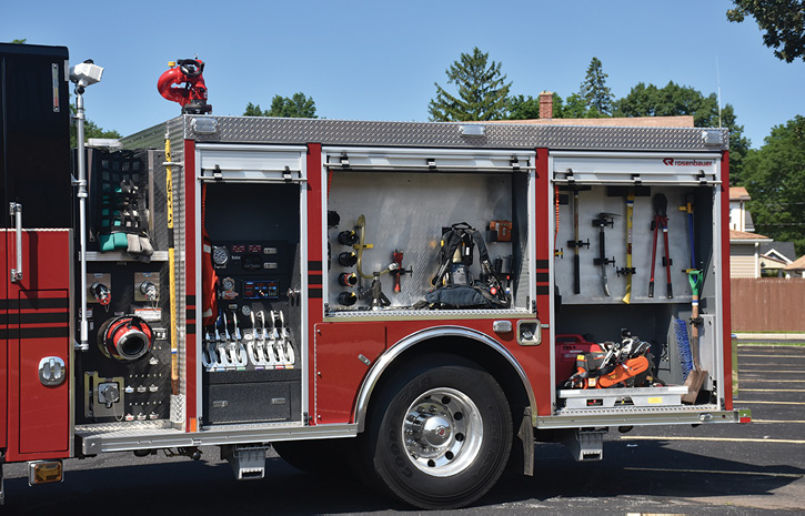 The driver's side narrow pump panel and large compartments with engine company fittings, forcible entry tools, and saw.