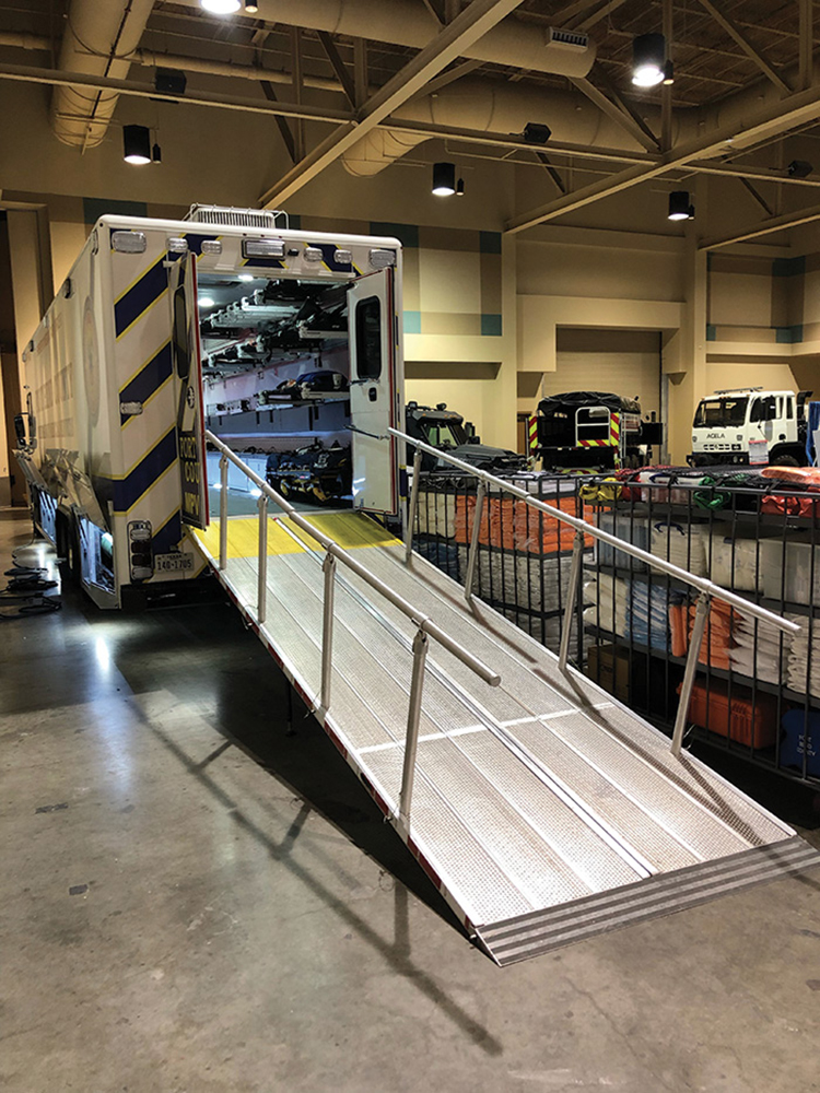 A large, bifold ramp with detachable hand rails stowed in between the rear truck frame rails provides access to an oversized rear door. A special transition plate bridges the apparatus and facility loading docks to make it easier to load entire hospital beds into the rear of the unit.