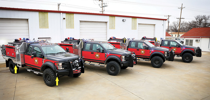 """Four identical Quick Attacks on Ford F-450 Quad Cabs for the Pottawatomie County District 1 in Kansas are lined up in front of the Weis """"wildland"""" fabrication shop. These rigs have 300-gallon tanks, onboard foam, and midbody ground sweep nozzles in addition to the two on the front bumper."""