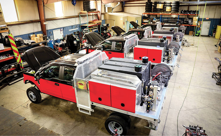 """An inside view of the """"wildland"""" fabrication shop showing the four rigs in photo 4 under construction."""