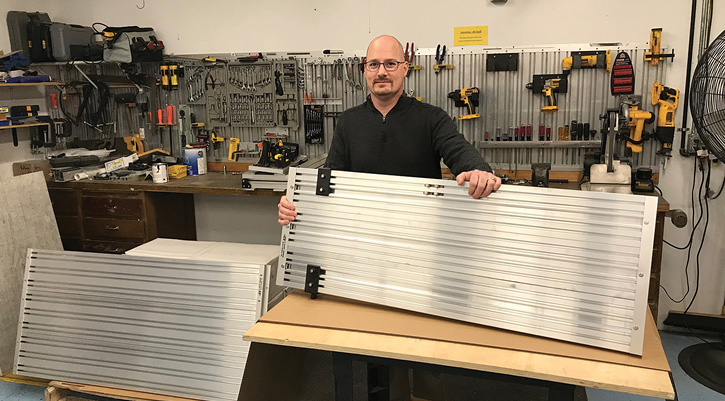 Greg Young, Performance Advantage Company's vice president and grandson of founder Dick Young, exhibits an extruded aluminum panel that is the heart of the company's apparatus tool mounting system.
