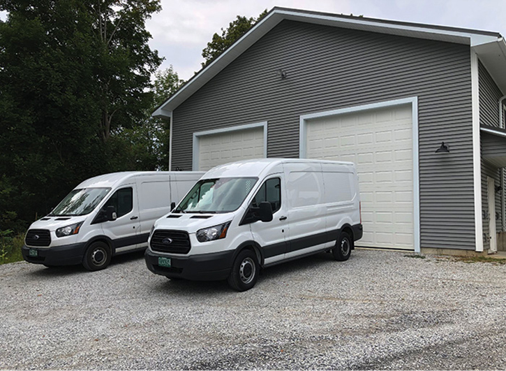 Two Desorcie service vans sit in front of their shop. If there were a siren sitting on top of the building and a Gamewell fire alarm box next to the door, it would look like a traditional New England fire station!