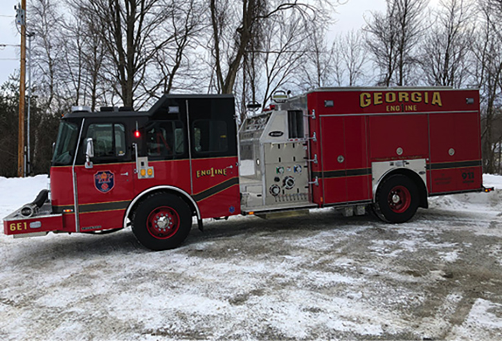 Georgia, Vermont, runs an E-ONE Typhoon custom cab aluminum top-mount rescue-pumper with a Hale 1,500-gpm pump and a 1,000-gallon tank. It features a preconnected hard sleeve on an extended front bumper for drafting out of a portable tank. It has a black-over-red paint scheme, raised cab roof, and hinged doors.