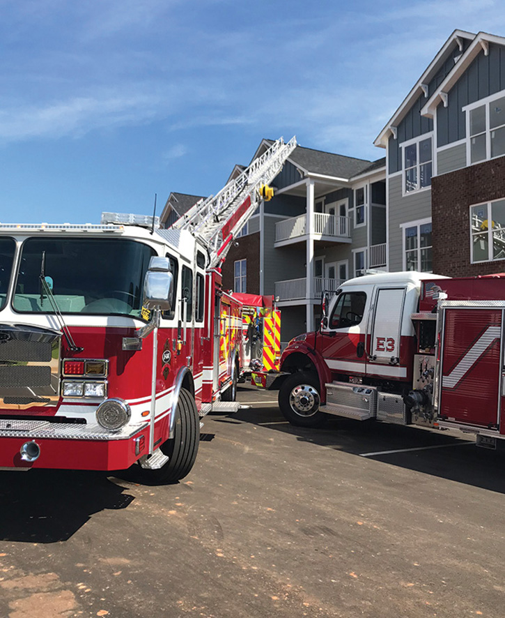 An E-ONE HP78 aerial ladder sets up in tight quarters at a housing complex.