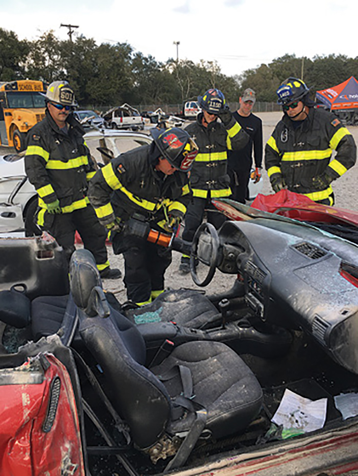 Hillsborough County firefighters watch a fellow firefighter's progress using one of Holmatro's battery-powered hydraulic rescue tools.