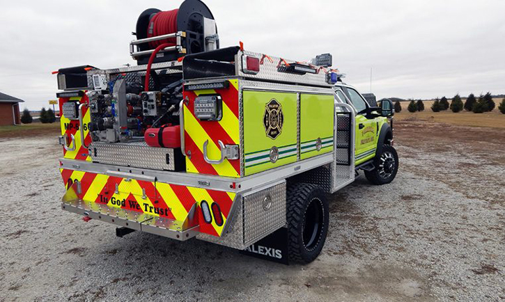 Rear of vehicle with rear-mount pump and flip-out hose hooks and booster reel with forestry line.