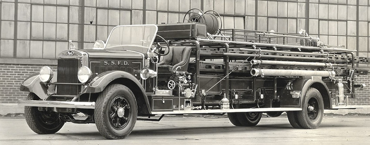 The open-cab quad was a very popular unit in small towns and cities throughout the United States. The quad with an enclosed crew cab and a side-to-side through walkway is a rarity. It shows an already long apparatus made longer.