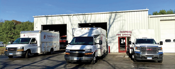 A few of its 14 road service trucks in front of apparatus service bays.
